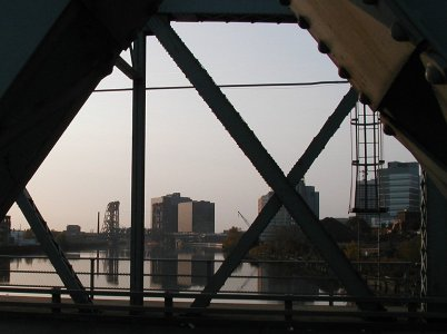 [Downtown bldgs framed by bridge elements, representational]