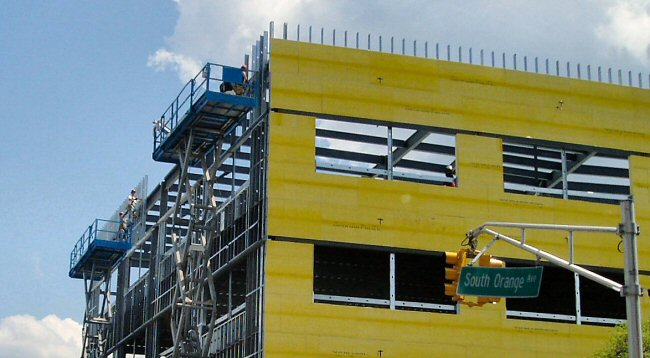 [Workmen putting up siding on NCC health center]